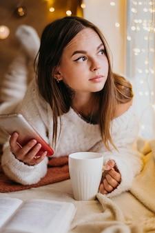 Mulher segurando uma xícara de chá enquanto desvia o olhar
