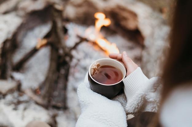 Mulher segurando uma xícara de chá quente