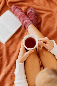 Mulher segurando uma xícara de chá
