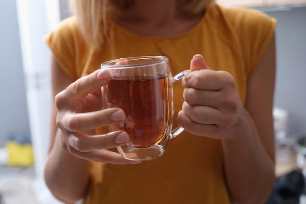 Mulher segurando uma xícara transparente de chá quente em close up de mãos