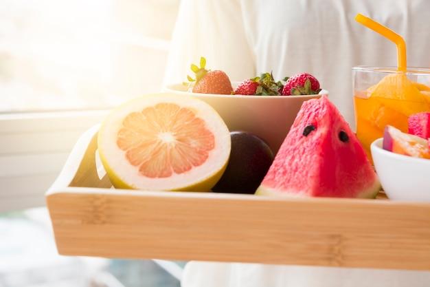 Mulher segurando várias fatias de frutas de toranja; melancia e morangos na tigela com copo de suco na bandeja de madeira