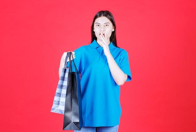 Mulher segurando várias sacolas de compras azuis e parece apavorada e confusa.