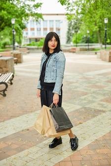 Mulher segurando vários sacos de papel, caminhando ao ar livre no parque