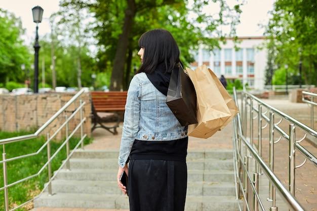 Mulher segurando vários sacos de papel com coisas compradas, caminhando ao ar livre no parque, garota depois das compras.