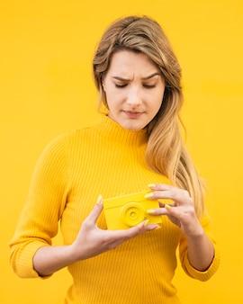 Mulher segurando velha câmera amarela
