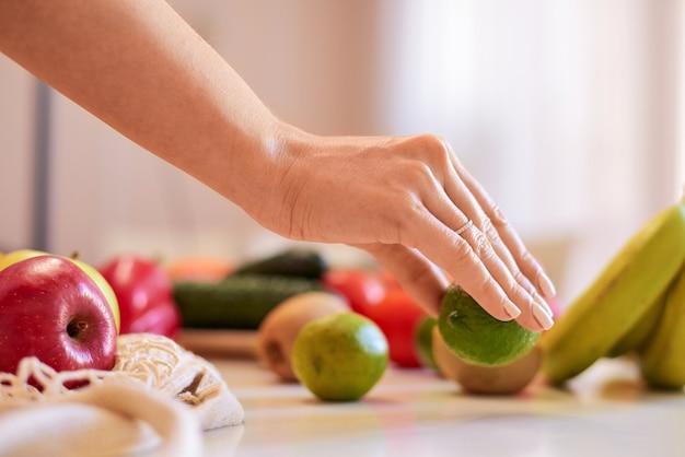 Mulher segurando verde limão com outras frutas