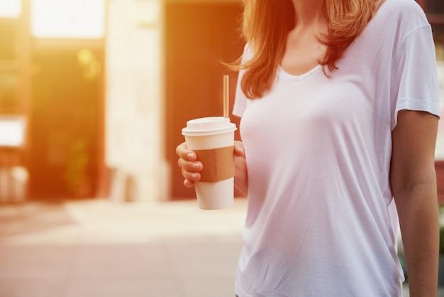 Mulher segurando xícara de café de papel na rua da cidade