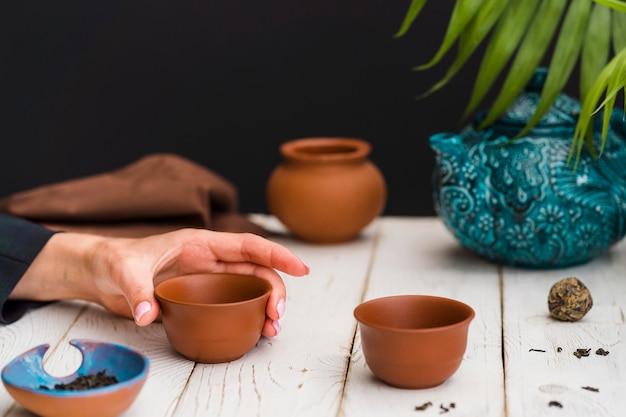 Mulher segurando xícara de chá de barro