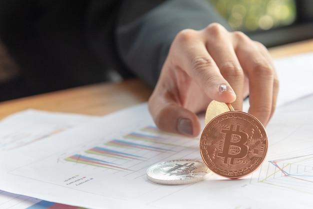 Mulher segurar bitcoin dourado em bitcoin prata e papel gráfico