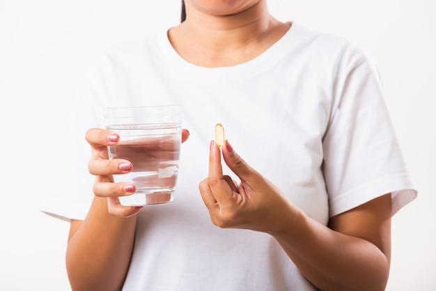 Mulher segurar drogas de vitamina de óleo de peixe na mão pronto tomar medicamentos com um copo de água