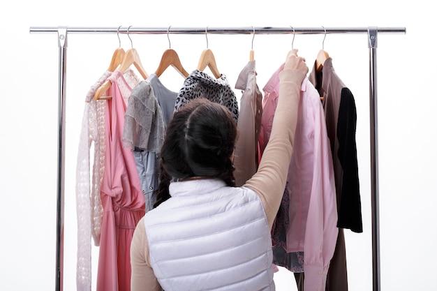 Mulher seleciona novas roupas da moda em cabides de madeira em rack em fundo branco. conceito de compras