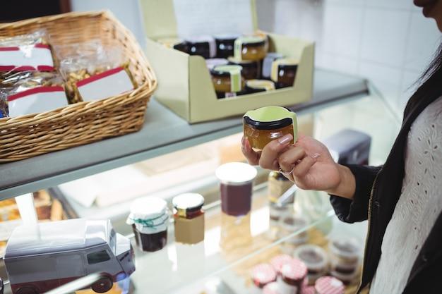 Mulher selecionando mel no balcão de comida