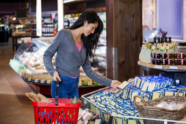 Mulher selecionando produtos lácteos na seção de compras