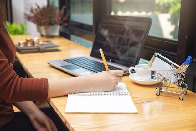 Mulher selecionar item do site shoppping on-line com cartão de crédito e moeda no carrinho de compras