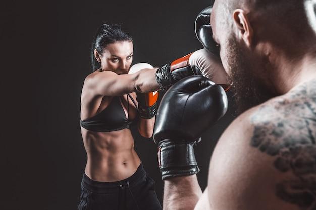 Mulher sem camisa, exercitando-se com o treinador na aula de boxe e defesa pessoal luta feminina e masculina