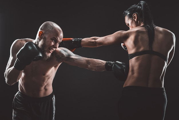 Mulher sem camisa se exercitando com o treinador na aula de boxe e defesa pessoal, estúdio, espaço escuro