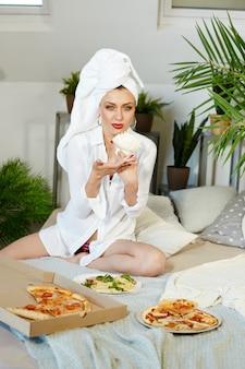 Mulher sem complexos come pizza e espaguete em casa. alegria e riso no rosto da mulher