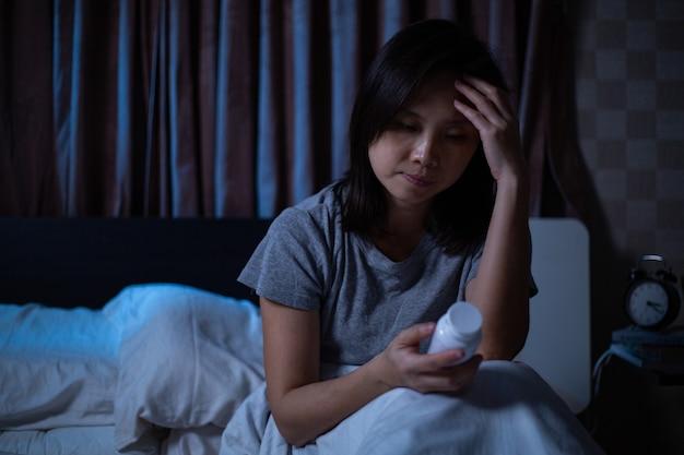 Mulher sem dormir, segurando o frasco de remédios para insônia, hora de tomar remédios para dormir à noite. menina asiática se preocupando com a vida depois de ter problemas.