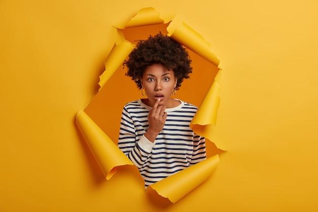 Mulher sem fala impressionada vê coisas terríveis, mantém a boca ligeiramente aberta, usa um macacão listrado, fica em pé no buraco de papel rasgado