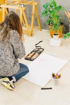 Mulher sem rosto desenhando no chão
