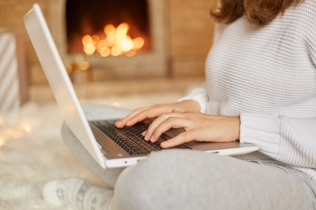 Mulher sem rosto digitando mensagem em seu laptop enquanto relaxa perto de uma fogueira quente, mulher desconhecida trabalhando online enquanto está sentada no chão com as pernas cruzadas, segurando o hotebook sobre os joelhos.