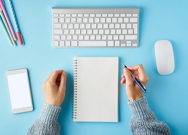 Mulher sem rosto, escrevendo no bloco de notas. telefone móvel com tela branca em branco.