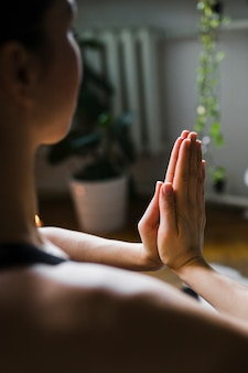 Mulher sem rosto meditando em casa