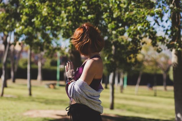 Mulher sem rosto meditando no parque