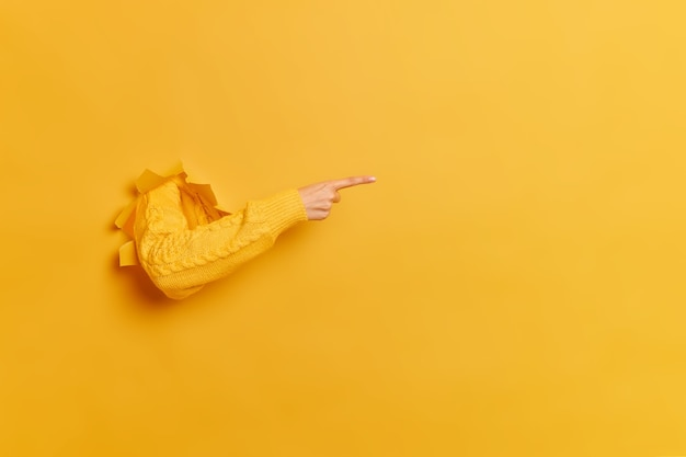 Mulher sem rosto quebra o braço através de papel parede amarela indica à direita no espaço em branco dá conselhos para comprar assinatura sugere clicar no link mostra a direção.
