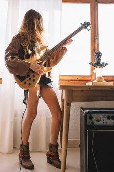 Mulher sem rosto tocando guitarra perto da mesa Foto gratuita