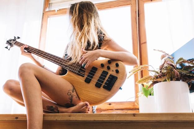 Mulher sem rosto tocando violão na mesa