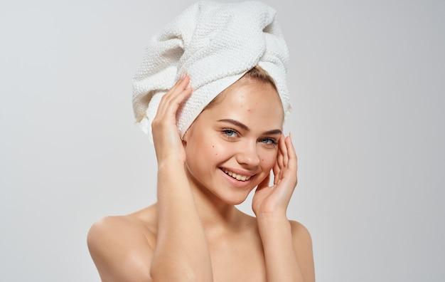 Mulher semi-nua endireita uma toalha em seu modelo de cabelo de pele limpa de cabeça.