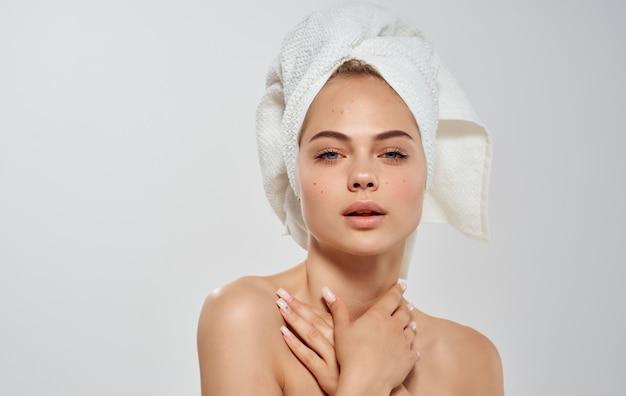 Mulher semi-nua endireita uma toalha na cabeça modelo de cabelo pele limpa
