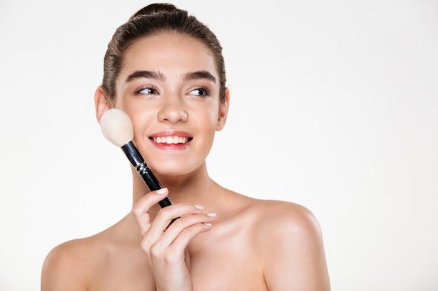 Mulher seminua atraente com pele fresca, segurando o pincel para maquiagem perto do rosto e olhando de lado