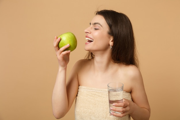 Mulher seminua com pele perfeita, maquiagem nude segura maçã e água isoladas na parede bege