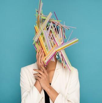 Mulher sendo coberta por canudos plásticos coloridos