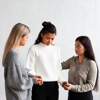 Mulher sendo consolada em uma sessão de terapia em grupo