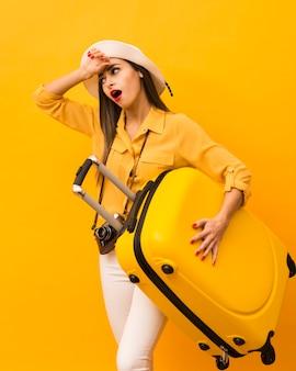 Mulher sendo exausta de carregar bagagem para viagem