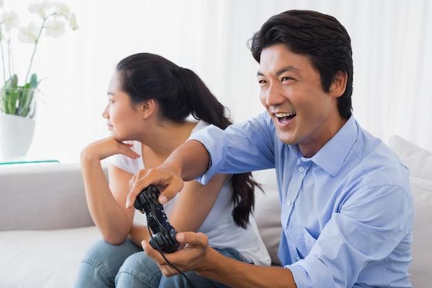 Mulher sendo ignorada pelo namorado jogando videogames