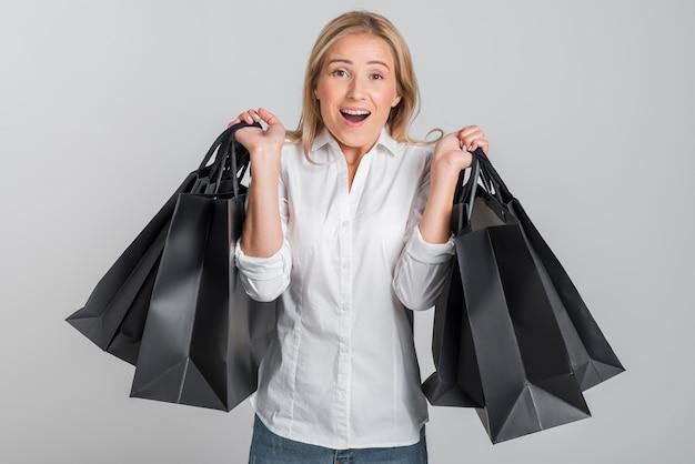 Mulher sendo oprimida pela quantidade de sacolas de compras que está segurando