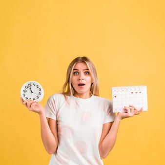 Mulher sendo surpreendida e segurando um relógio e um calendário menstrual