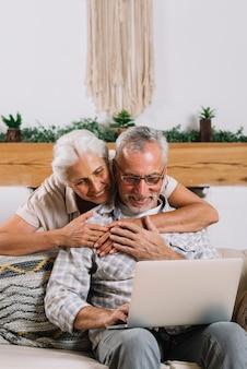 Mulher sênior, abraçando, dela, marido, usando computador portátil