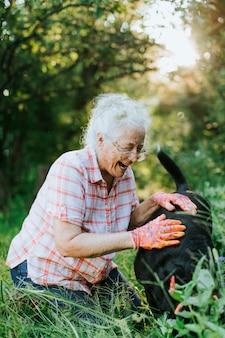 Mulher sênior, acariciar, dela, cão, jardim