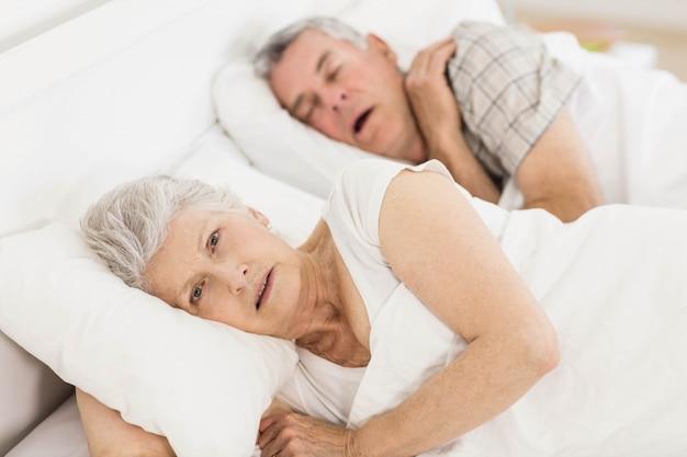 Mulher sênior acordada na cama enquanto seu marido está roncando