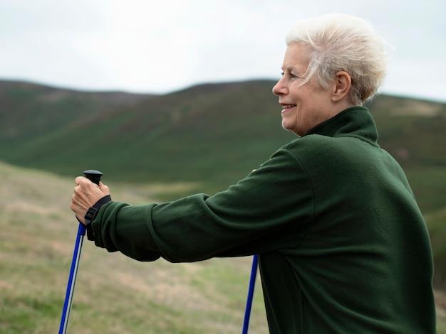 Mulher sênior, andar, com, trekking, polos