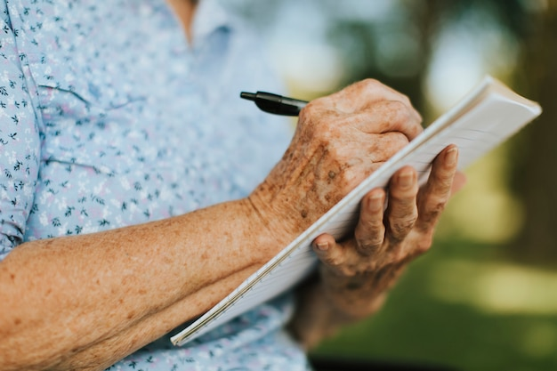 Mulher sênior, anotando suas memórias em um notebook