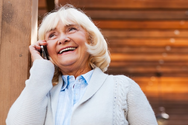 Mulher sênior ao telefone. mulher sênior feliz falando no celular e sorrindo enquanto fica ao ar livre
