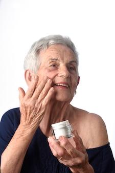 Mulher sênior, aplicando, creme pele, ou, moisturizer, para, dela, rosto