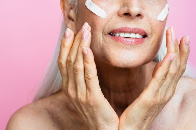 Mulher sênior, aplicar cuidados com a pele no rosto