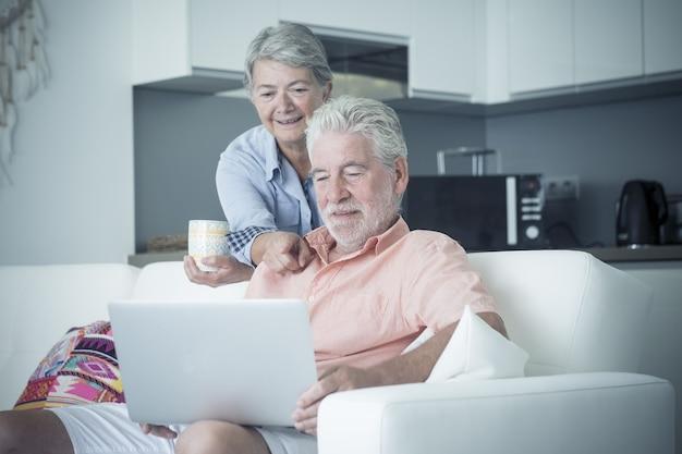 Mulher sênior apontando para o laptop enquanto o marido o usa. mulher idosa segurando a xícara de café enquanto olha para o laptop. casal idoso assistindo conteúdo de mídia usando laptop em apartamento moderno